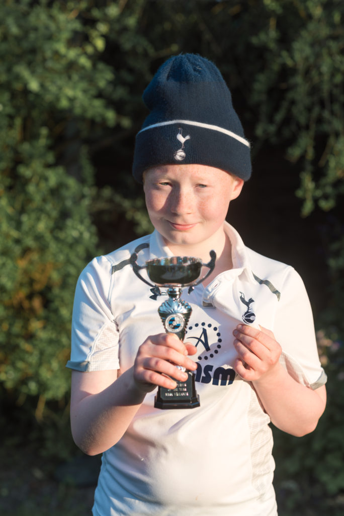 Mark, dressed up in Tottenham Hotspur gear and holding a trophy for Team Player Of The Year in the side he played for.