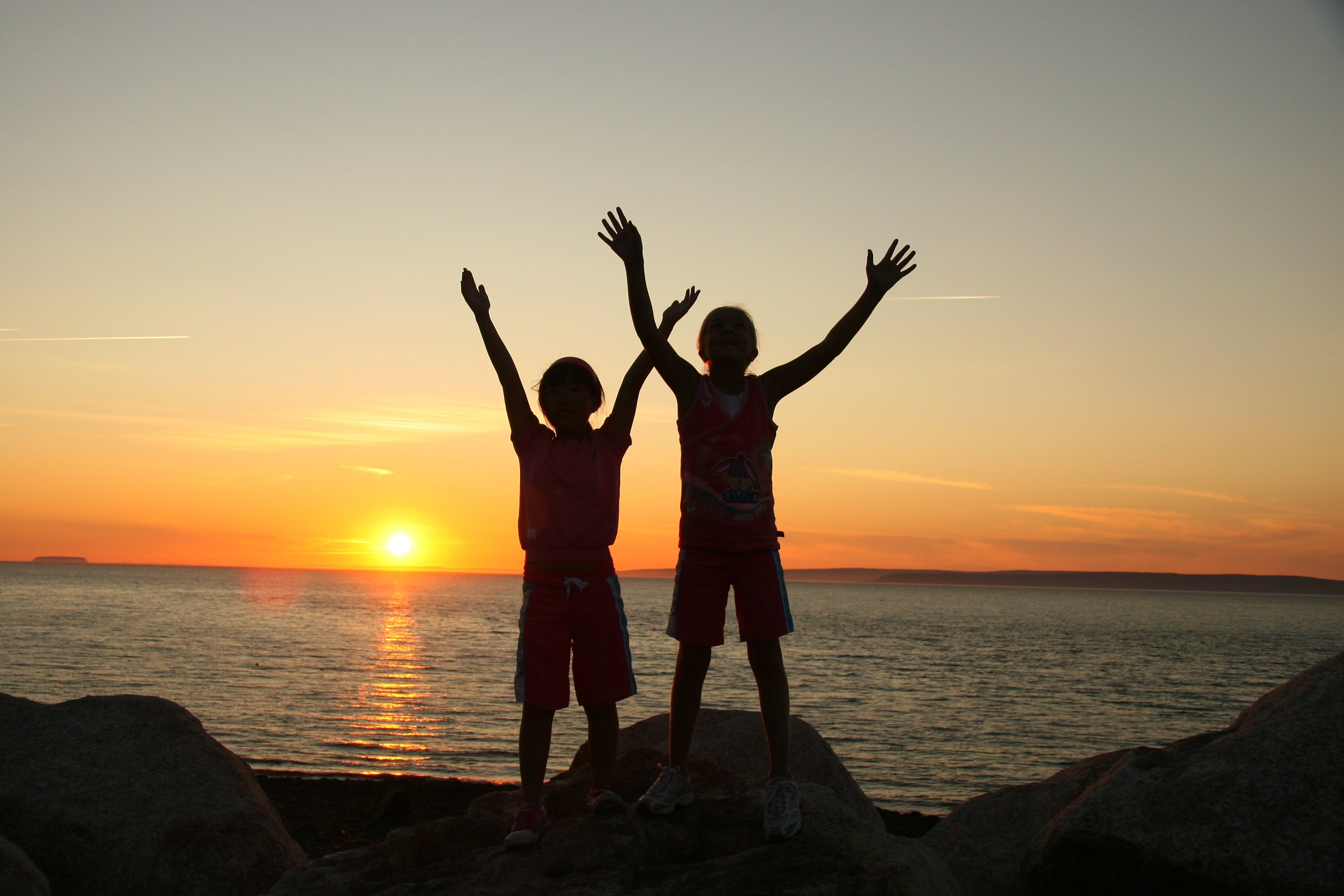 Silhouettes of two children in front of sunset over the ocean